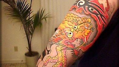 Татуировка кровожадного дракона, обвивающего руку